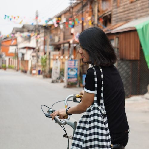 Side view of woman riding bicycle on street