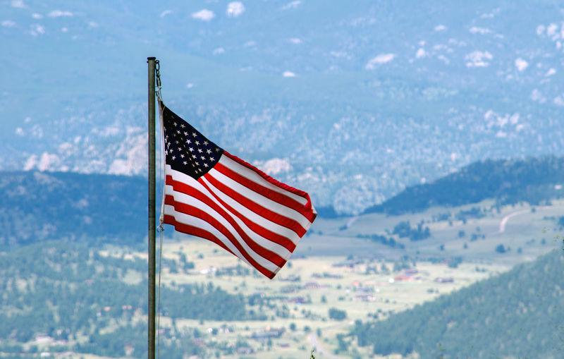 An america flag flies over the colorado rocky mountains.