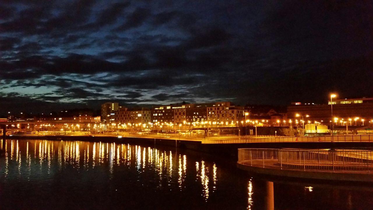 Illuminated Lights Reflecting On River At Night