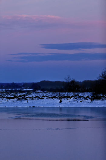 Scenic view of frozen land against sky at sunset
