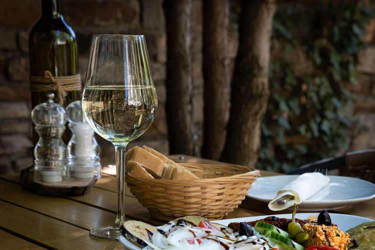 Drinking glass and bread basket on table
