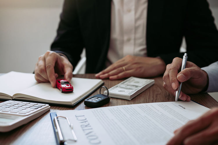 Cropped hands of customer signing contract with car salesperson sitting at desk