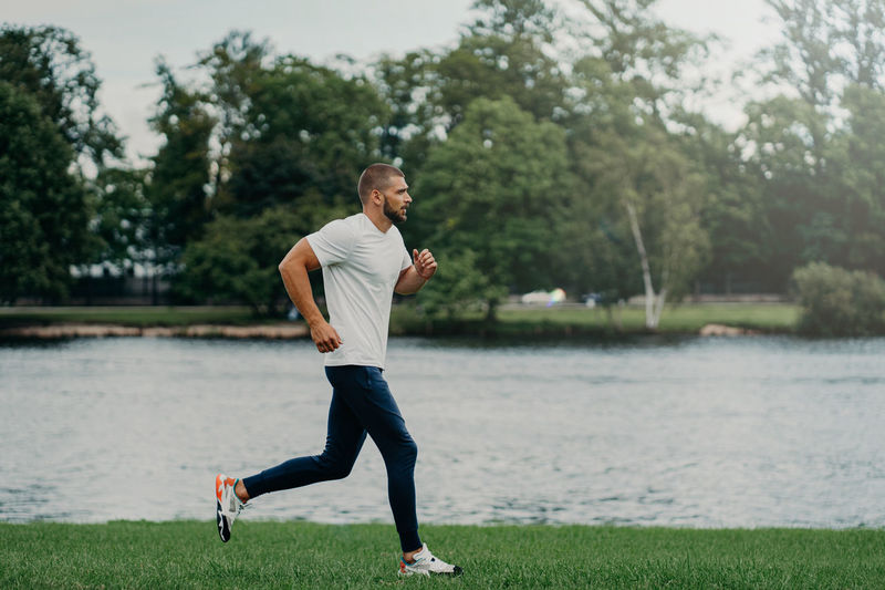 Full length of man jogging by lake against trees