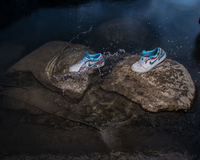 High angle view of shoes on rock in lake