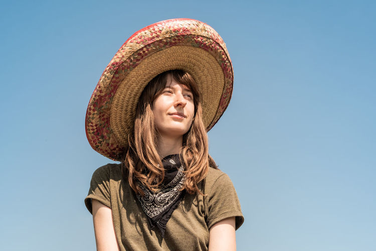 Low Angle View Of Thoughtful Young Woman Wearing Cowboy Hat While Standing Against Clear Sky