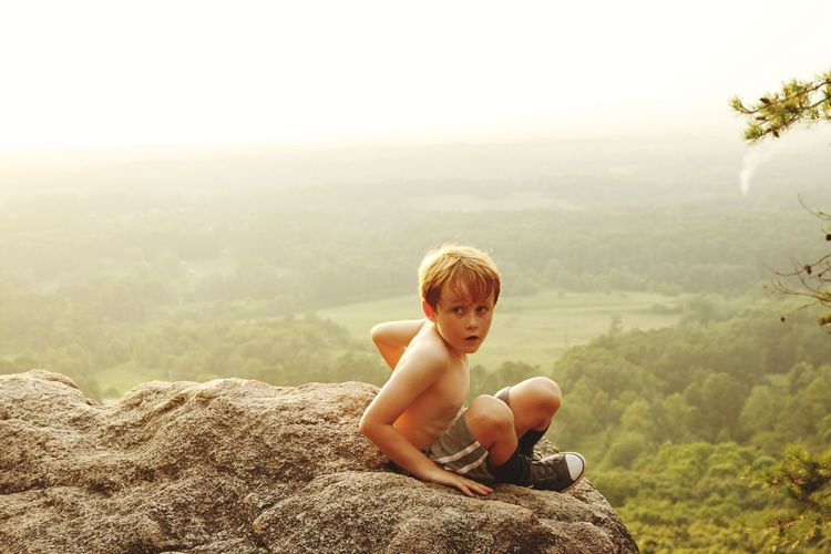 High angle view of boy sitting on cliff against landscape