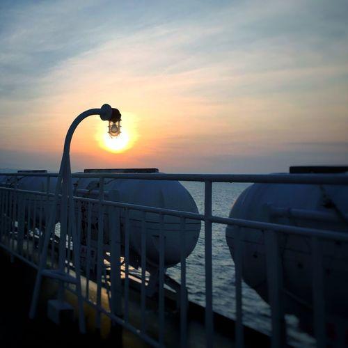 Street Light By Railing Against Sunset Sky