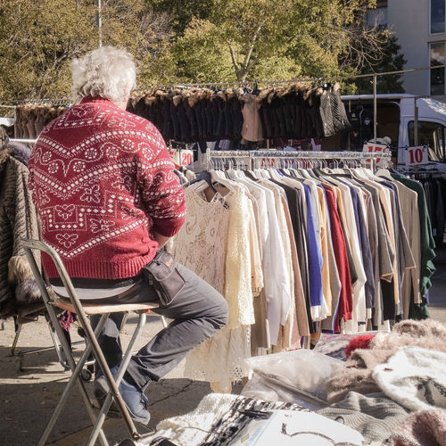 Adult Adults Only Business Finance And Industry Choice Clothes Clothes Rack Day Man Market Market Stall Marketplace Old One Person One Woman Only Outdoors People Retail  Seller Selling Selling On The Street Variation Waiting
