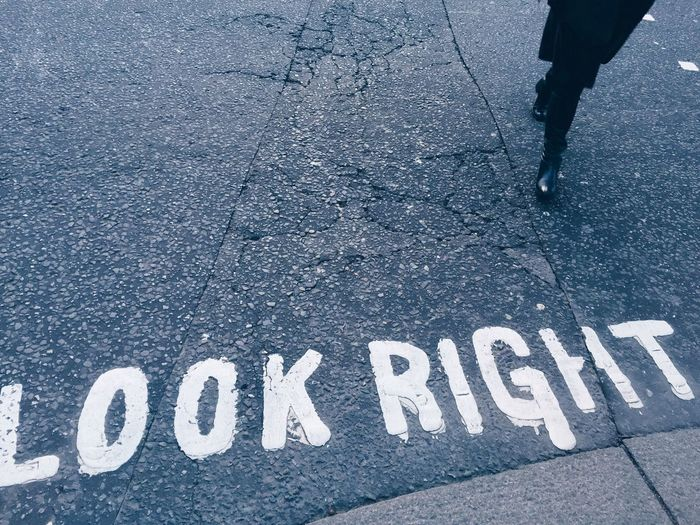 High angle view of text with person walking on road