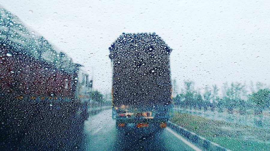 Trucks Seen Through Wet Window In Rainy Season