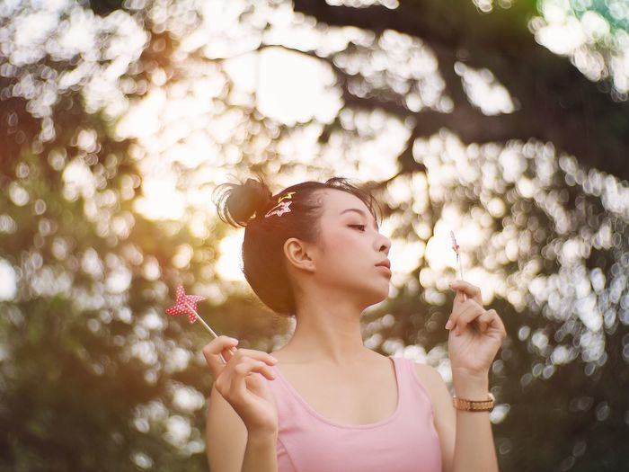 Low angle view of woman looking pinwheel toy against tree