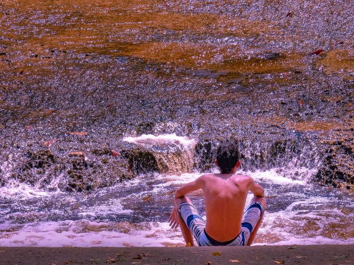 Shirtless man sitting at riverbank