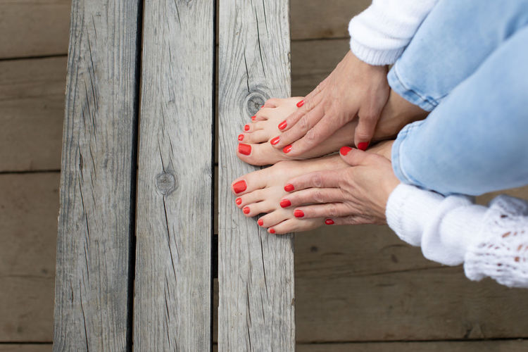 Low section of woman with nail polish on wooden seat