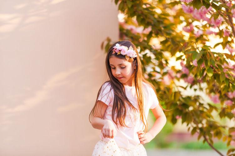 Smiling girl standing against flowering tree