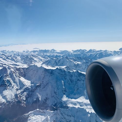 Airplane flying over snowcapped mountains