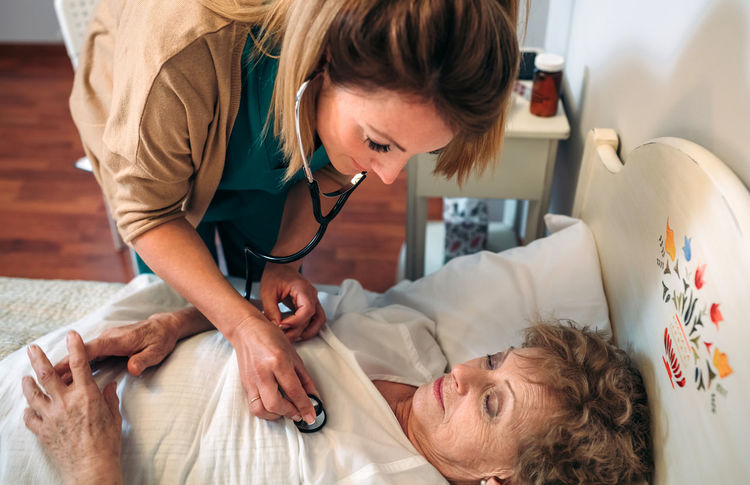 Female caregiver auscultating senior woman at home Bed Care Doctor  Horizontal Hospital Nursing Woman Aged Auscultation Clinic Elderly Examining Health Care Healthcare And Medicine Heart Home Assistance Home Assistant Illness Medical Nursing Home Patient Senior Stethoscope  Treatment Two People