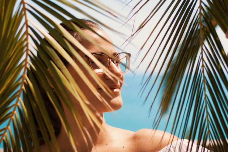 Close-Up Of Woman Wearing Eyeglasses Seen Through Palm Leaves At Beach