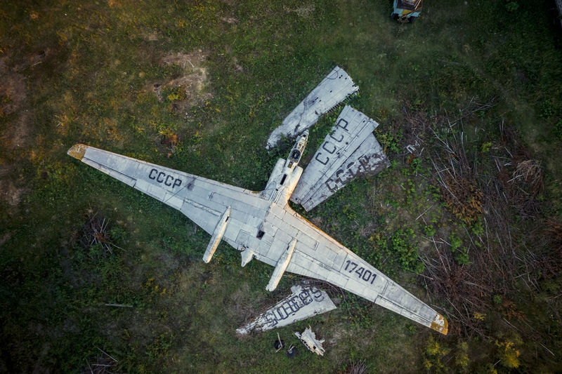High angle view of abandoned airplane flying over field