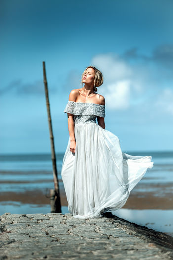 Woman in dress standing at beach against sky