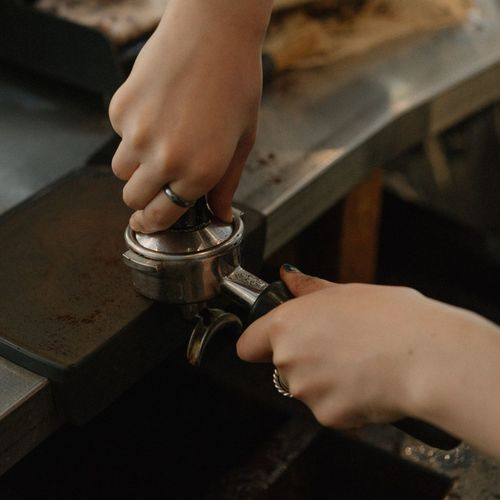 Cropped Hands Of Woman Preparing Coffee In Cafe
