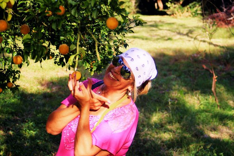 The happiness of being in nature and enjoying the fruits Feliz Woman Fruits Color One Person Women Tree Females Lifestyles Real People Outdoors Plant