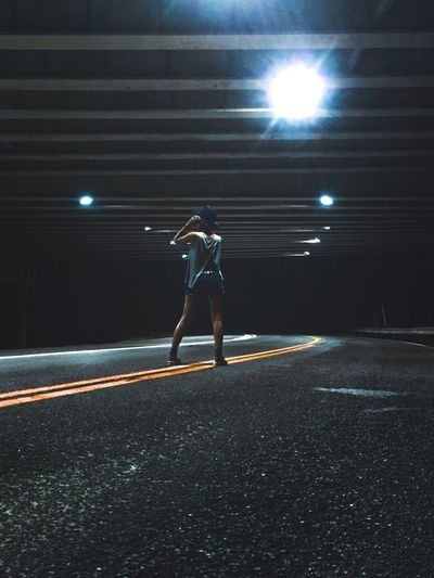 Rear View Of Woman Standing On Road Under Bridge At Night