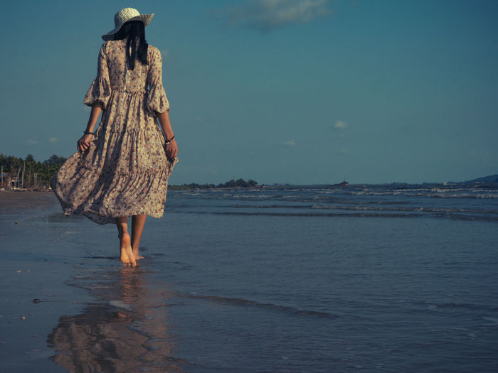 Women who wear vintage dresses are walking on the beach with excitement to relax. This summer, let's go to the sea. Water Sea Land Sky Nature Beach Real People One Person Day Women Scenics - Nature Motion Lifestyles Rear View Leisure Activity Beauty In Nature Low Section Vacations Trip Outdoors