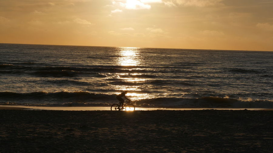 Beach Beauty In Nature Bike Ride Biker Horizon Over Water Idyllic Nature Ocean, Waves, Nature One Person Outdoors Biketour Reflection Sand Scenics Sea Silhouette Ride Into The Sunset Sun Sunlight Sunset Tranquil Scene Tranquility Vacations Water Wave
