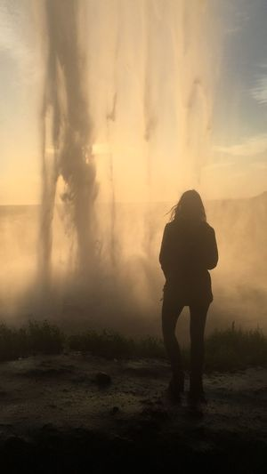 Rear view silhouette of woman standing by hot spring against sky during sunset