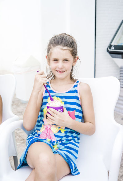 Girl in blue eating ice cream at the beach front ice cream parlour Eating Beach Promenade Blue Casual Clothing Child Childhood España Females Front View Girl Girls Happiness Holding Ice Cream Ice Cream Parlour Innocence Mulitcolored One Person Outdoors Seat Sitting Smiling Spaın Three Quarter Length White Background