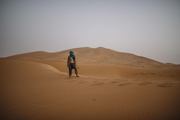 Full length of woman on sand dune in desert against clear sky