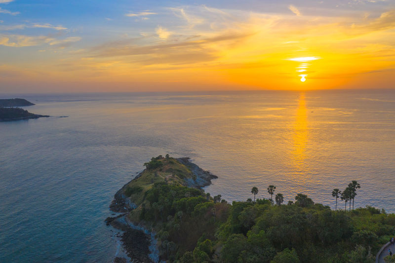 aerial photography sunset at Laem Promthep Cape viewpoint. Promthep cape is the most popular viewpoint in Phuket. the most tourist always come to see sunset at this landmark Phuket,Thailand Promthep, Cape, Dracula, Venice Sugar Palm, Sky Sunset Cloud - Sky Scenics - Nature Beauty In Nature Nature Water Horizon Over Water Travel Tourism Destination Popular, Thanks! Sea Orange Color Tranquility Tranquil Scene Horizon Idyllic Rock Land Rock - Object Solid Beach Outdoors