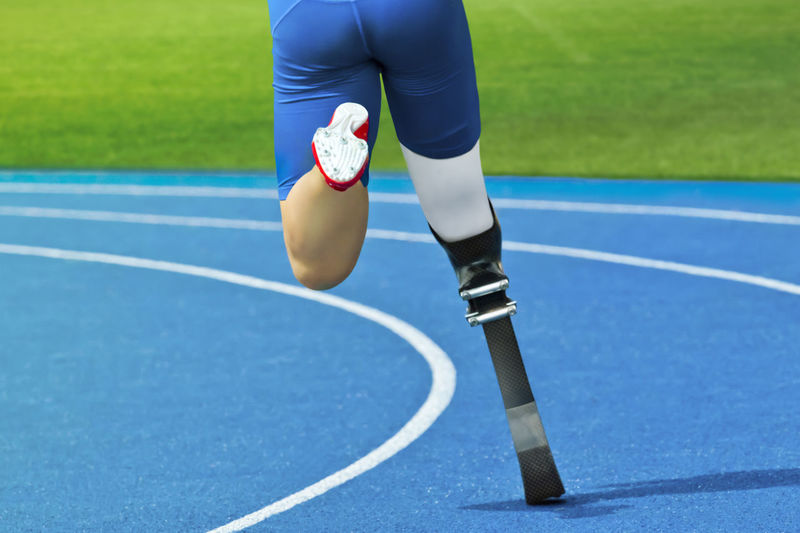 Low section of athlete running with prosthetic leg on track