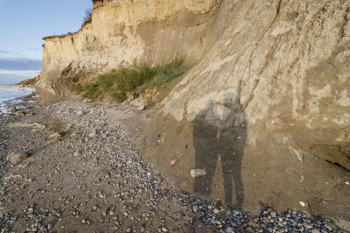 Shine Sunlight Adult Adults Only Day Nature One Man Only One Person Only Men Outdoors People People Shadow Real People Rock - Object Sand Sea Shadow Standing Steep Coast Steep Coastline Stone Stone Material Stone Object Stones Sunset Visual Creativity