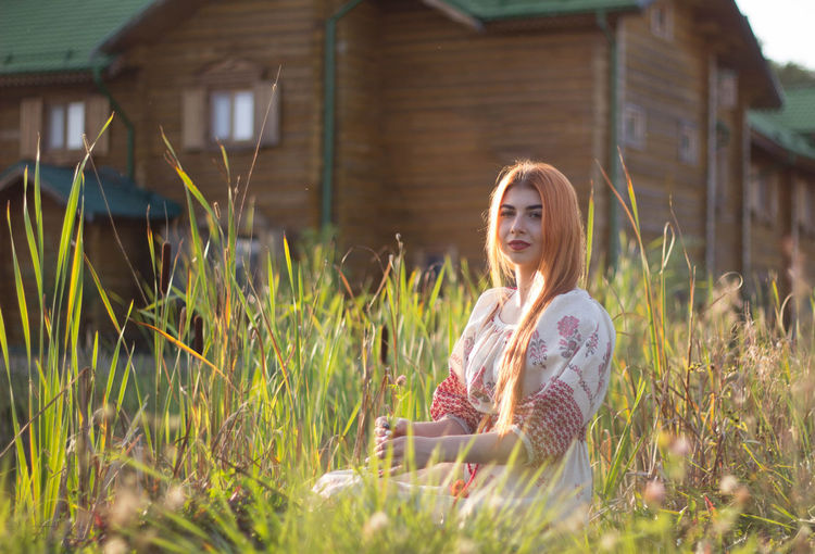 Young woman sitting on grass at field