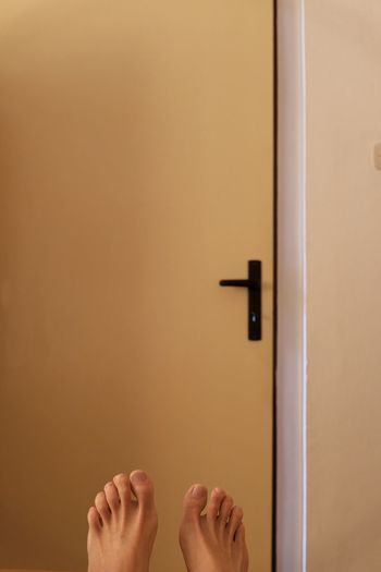Low section of woman standing by door at home