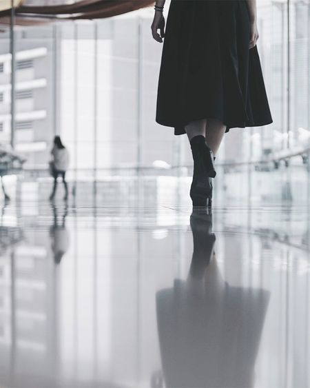 Low section of woman walking with reflection