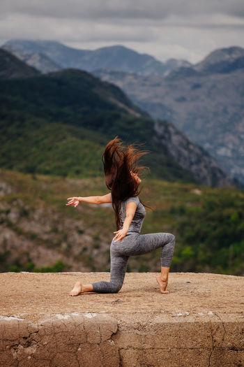 Side view full length of woman exercising on cliff against mountains
