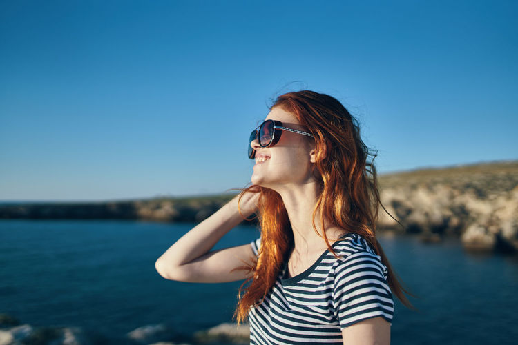 Woman wearing sunglasses standing against sea against clear sky