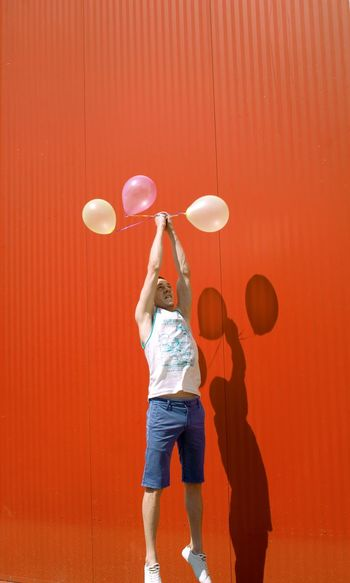 Man With Balloons Levitating Against Red Wall