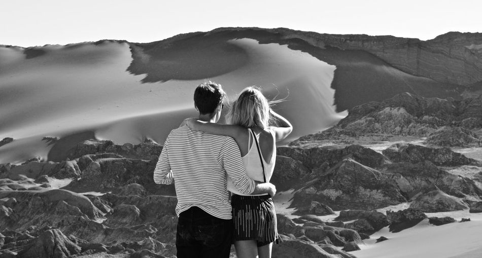 Rear view of couple standing on mountain against sky