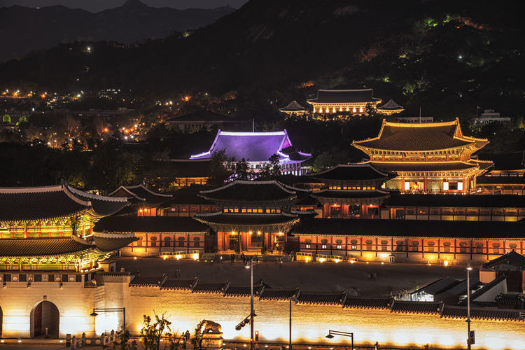 Gyeongbokgung Palace At Night in seoul South Korea,with the name of the 'Gyeongbokgung' on a sign. Architecture Asian; Old; City; Architecture; Ancient; Historical; Royal; Building Building Exterior Built Structure City Culture; Autumn; Tourist; Gyeongbok; Sky; Grounds; Dress; Hanbok; Garden; Gwanghwamun; Castle; Gateway; Blue; Beautiful; Nature; Flowers Girl; Tourism; Gate; Summer; Historic; Oriental; Glowing Gyeongbokgung; Korea; Seoul; Palace; South; Korean; Illuminated Lighting Equipment Nature Night No People Outdoors Place Of Worship Traditional; Travel; Asia; Woman; Landmark; Building; Travel Destinations Tree Water