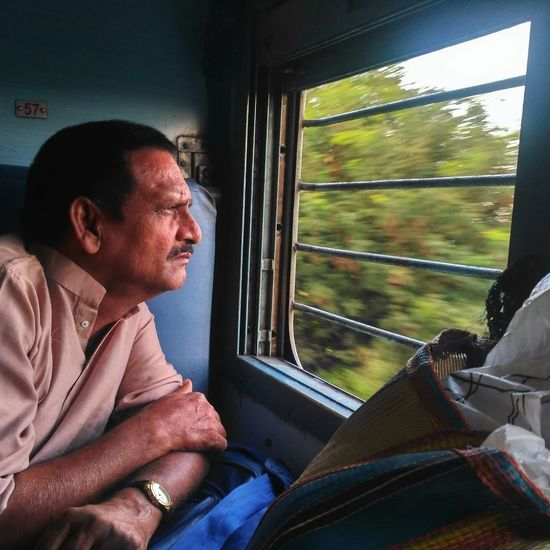 Side View Of Mature Man Looking Towards Train Window