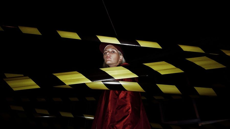 Portrait of woman standing by cordon tapes at night
