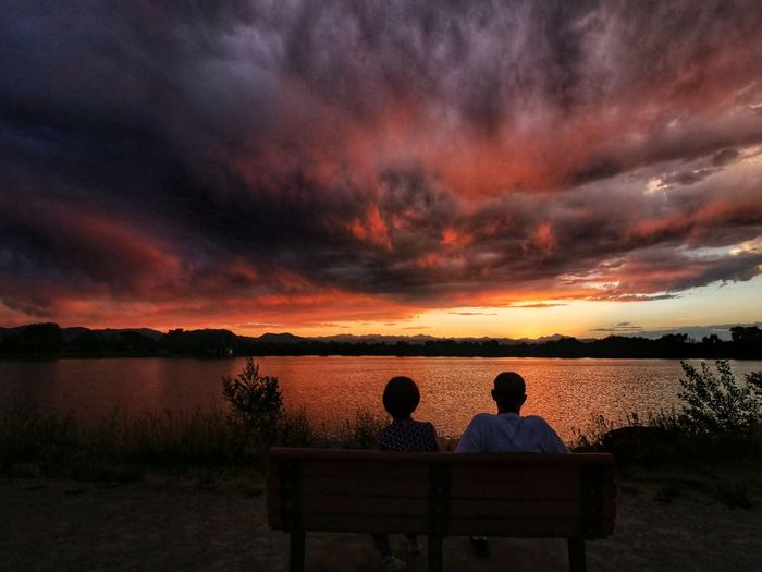 Rear view of couple sitting on shore against sunset sky