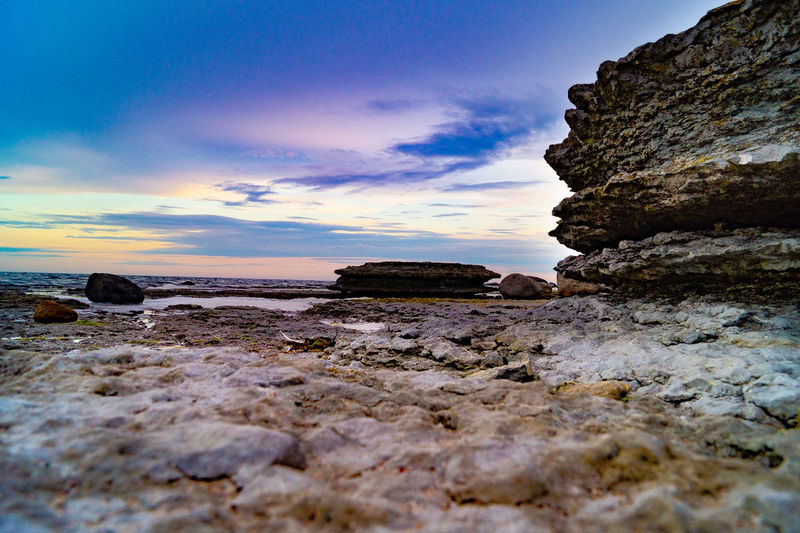 Surface level of rocks on shore against sky during sunset