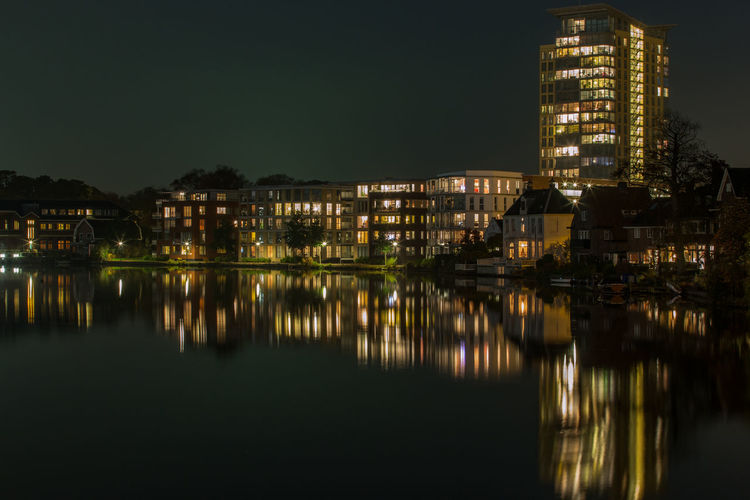 Illuminated buildings reflecting in river against sky at night