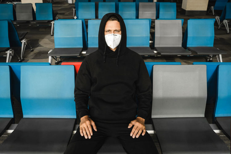 Portrait of man wearing mask while sitting in waiting room