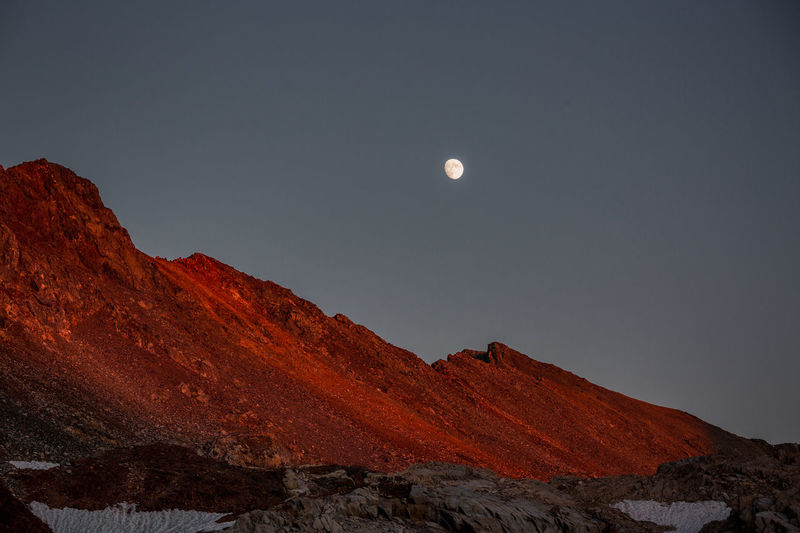 Unfolding before my eyes JMT DAY 17 - MOONRISE AND SUNSET AT HELEN LAKE Moonrise and sunset at Helen Lake Helen Lake was only a mile down the slope from Muir Pass, so we didn't rush. However, we had been told that finding a campsite could be a slight challenge, so we decided to get off the pass earlier than later. What we didn't know was that it was extremely windy as if we were in a wind tunnel. The strong wind that never seemed to die down gave us a hard time pitching our tents. For a better vantage point, I decided to find a spot rather higher. From where I was, the sun looked like setting over Muir Pass. At that very moment I wondered what it would look like to watch the sun set from the pass. There were campsites near Muir Hut but it wasn't an option due to lack of water, besides the fact that it was super windy. It turned out that Helen Lake wasn't much different. The not so bright glow cast on Black Divide soon turned into a bright orange as if somebody just painted it in a quick brush work of orange in a blink of an eye. And then an insanely glowing red. While my eyes were transfixed on the mesmerizing glow in spite of the crazy shiver I couldn't seem to stop, unfolding before my eyes was one of those unexpected and yet coolest. Moonrise over the divide cast in insane red! I knew the moon would rise and wash out the Milky Way, but I really didn't see this coming. What a sight to end the day! Helen Lake, Kings Canyon National Park, CA Moon Sky Mountain Beauty In Nature Scenics - Nature Tranquil Scene Tranquility Idyllic Clear Sky Outdoors Landscape Nature Mountain Range Low Angle View JMT John Muir Trail Kings Canyon Wilderness Sunset