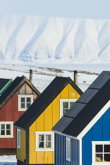 Houses by snowcapped mountains against sky